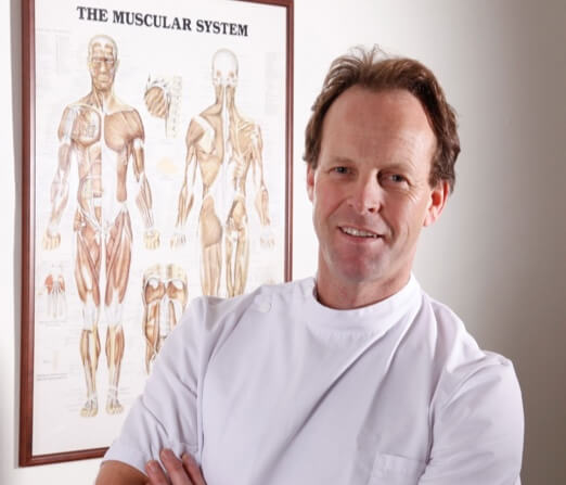 Rob wearing white coat in front of The Muscular System poster